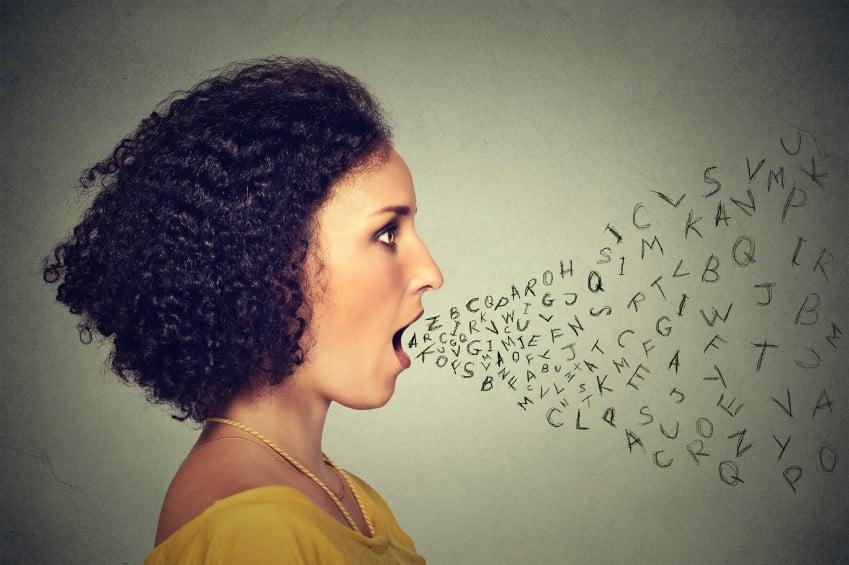 Femme parlant avec des lettres de l'alphabet sortant de sa bouche.  Communication, information, concept de renseignement